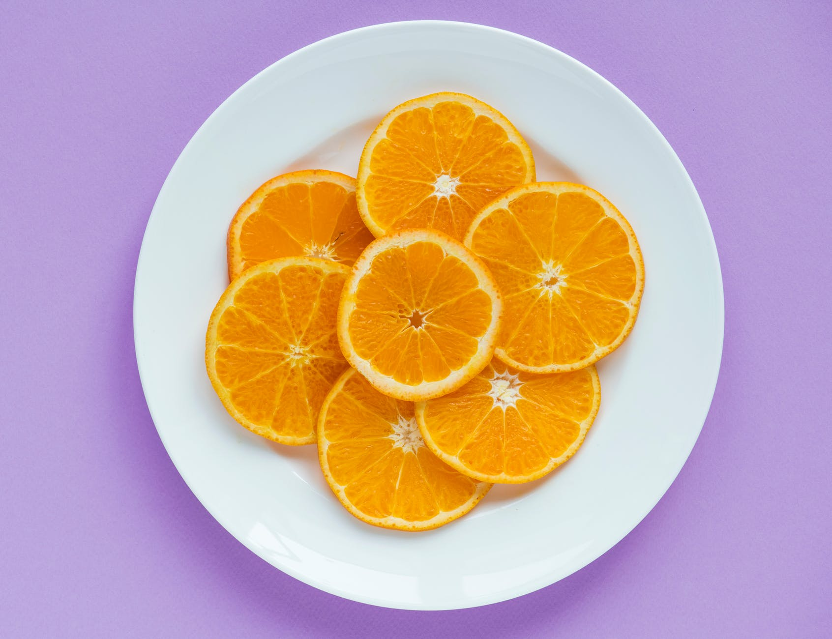 sliced orange fruits on round white ceramic plate